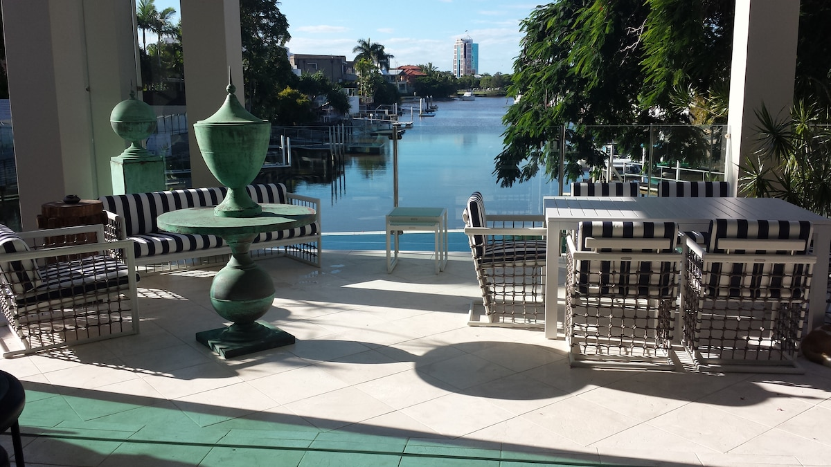 Outdoor lounge suite, table and chairs overlooking the water