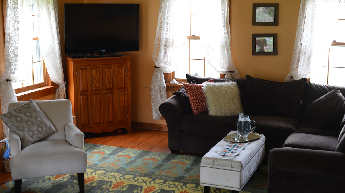 Cozy living room with big screen tv, sectional couch, fireplace and two chairs (breakfast nook not pictured)