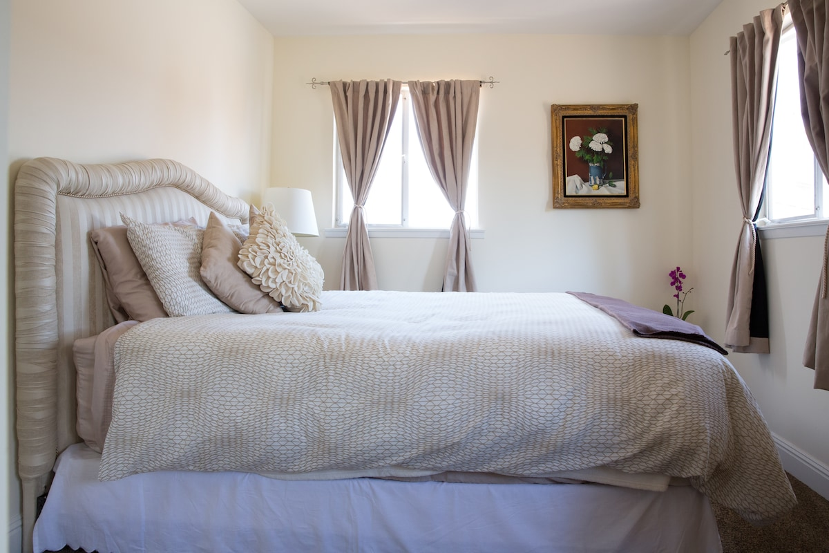 Comfortable queen size bed with lots of windows for fresh air.