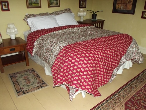 Large bedroom with queen-sized bed with views of the meadows, yard, flowers, woods and hills.