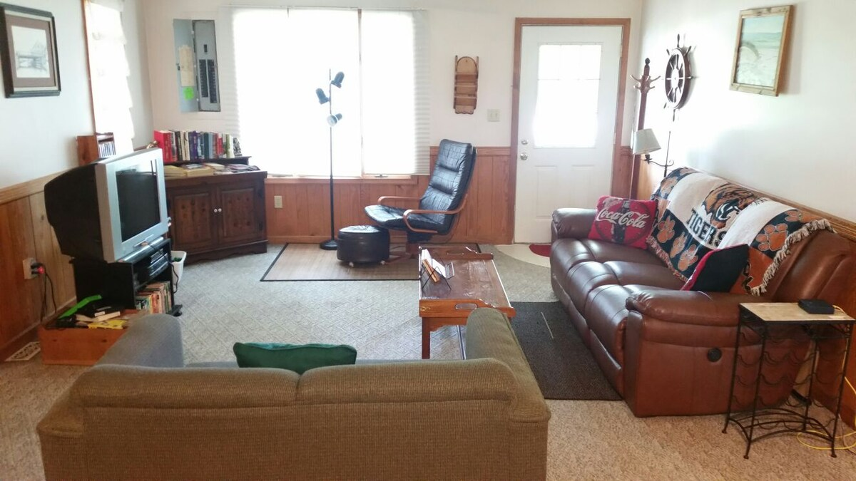 Living room with Dish Network TV, and console stereo, double recliner leather sofa, love seat, and chair with ottoman.