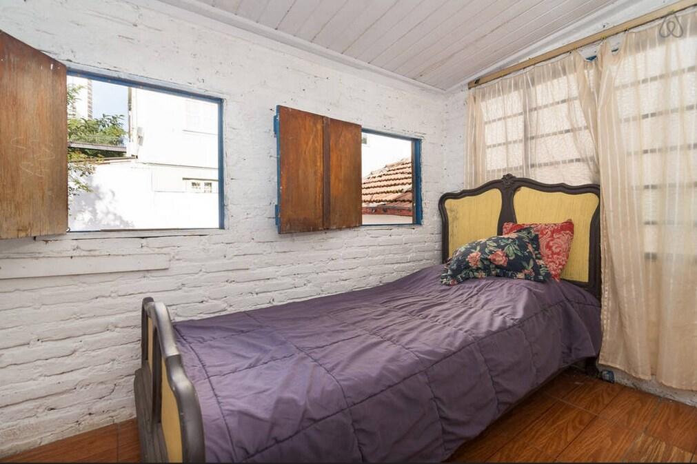 foto atual do quarto, simples porém aconchegante e bem iluminado, com 3 janelas