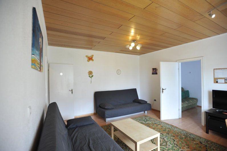 living room with 2 double sofas, TV and table with 4 chairs