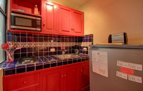 The kitchen  features cooktop, microwave, refrigerator and small appliances
