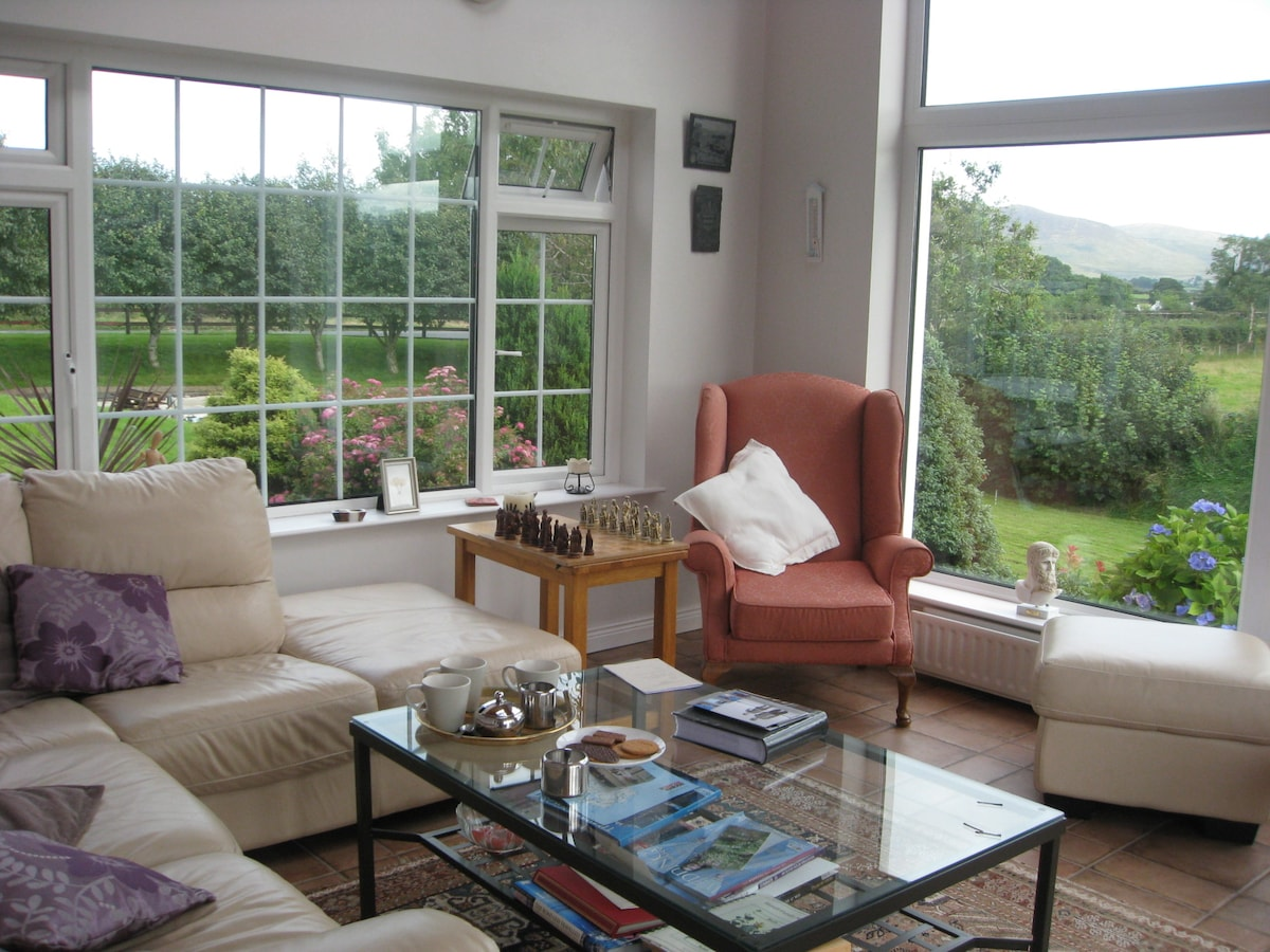 Spacious sun lounge with view of the Mourne Mountains .