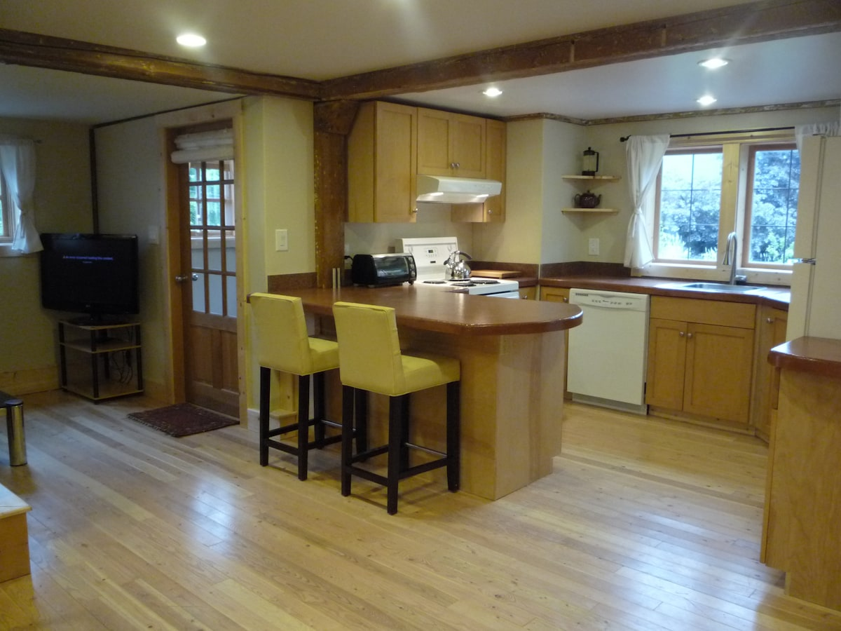 Fully equipped kitchen with breakfast bar. Also shows the entrance from the mudroom.
