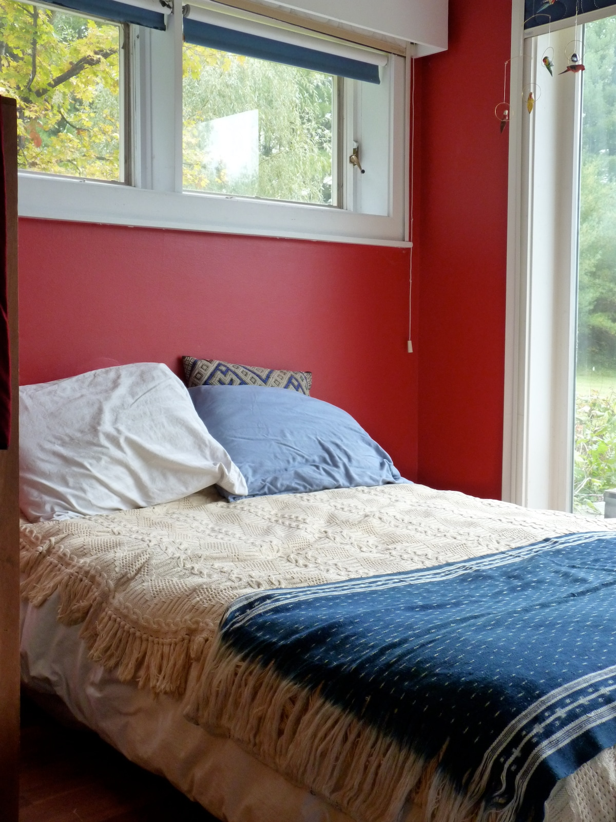 This bedroom has a double bed and sliding glass door looking out to the lawn.