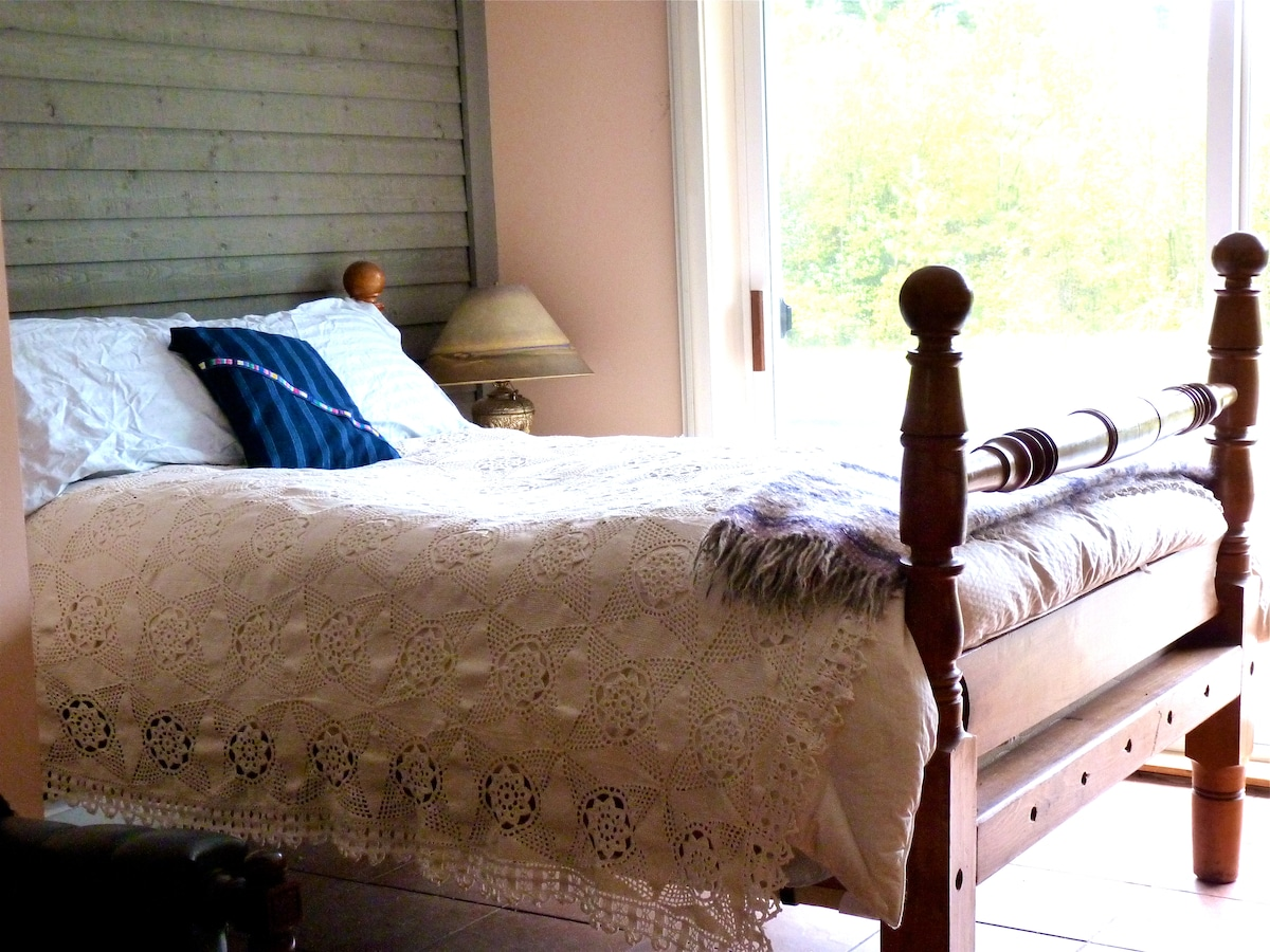 This is the double bed with an antique coverlet.