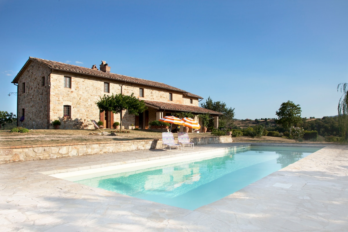 swimming pool with sun loungers, parasols and old stone country house