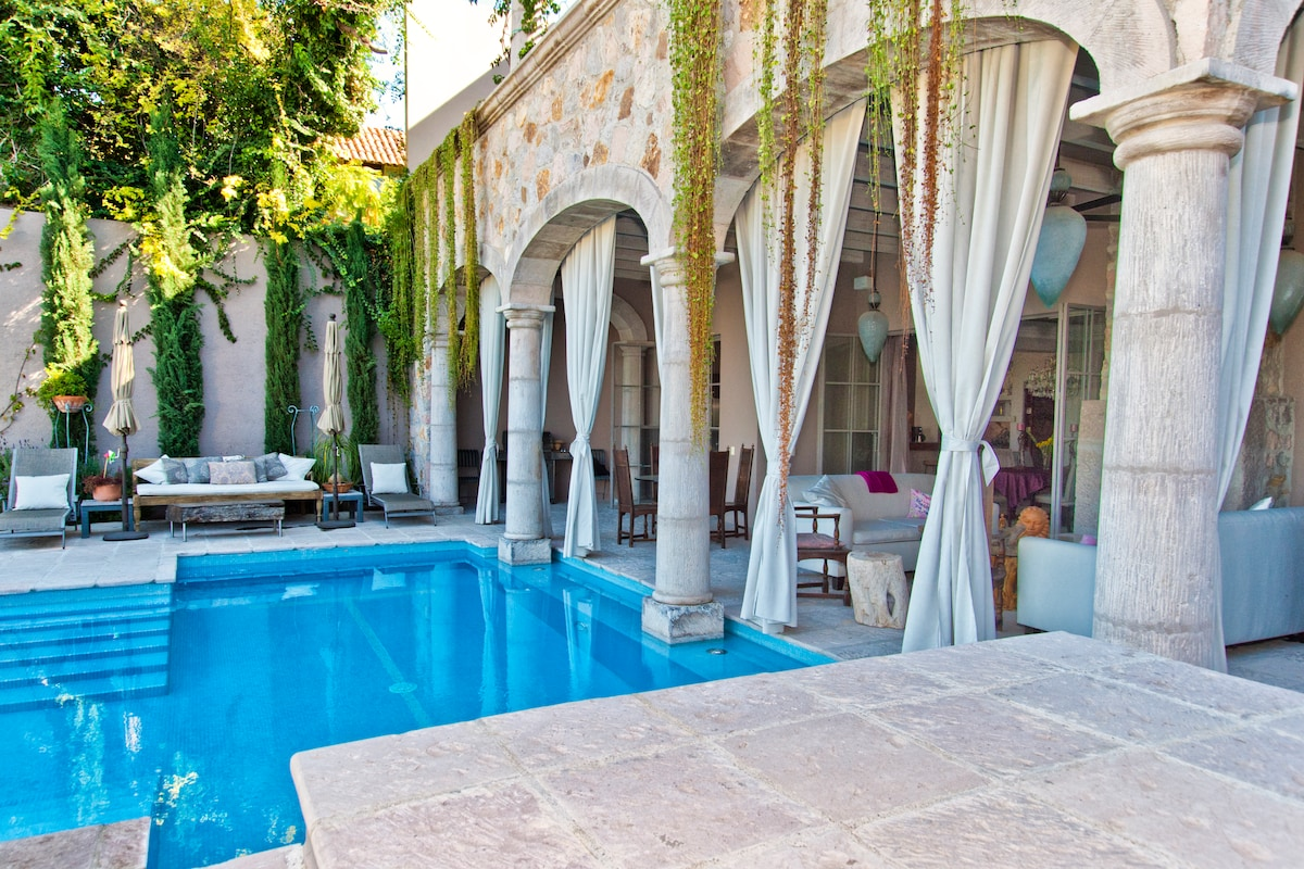 Villa with heated pool and outside living room with fireplace.