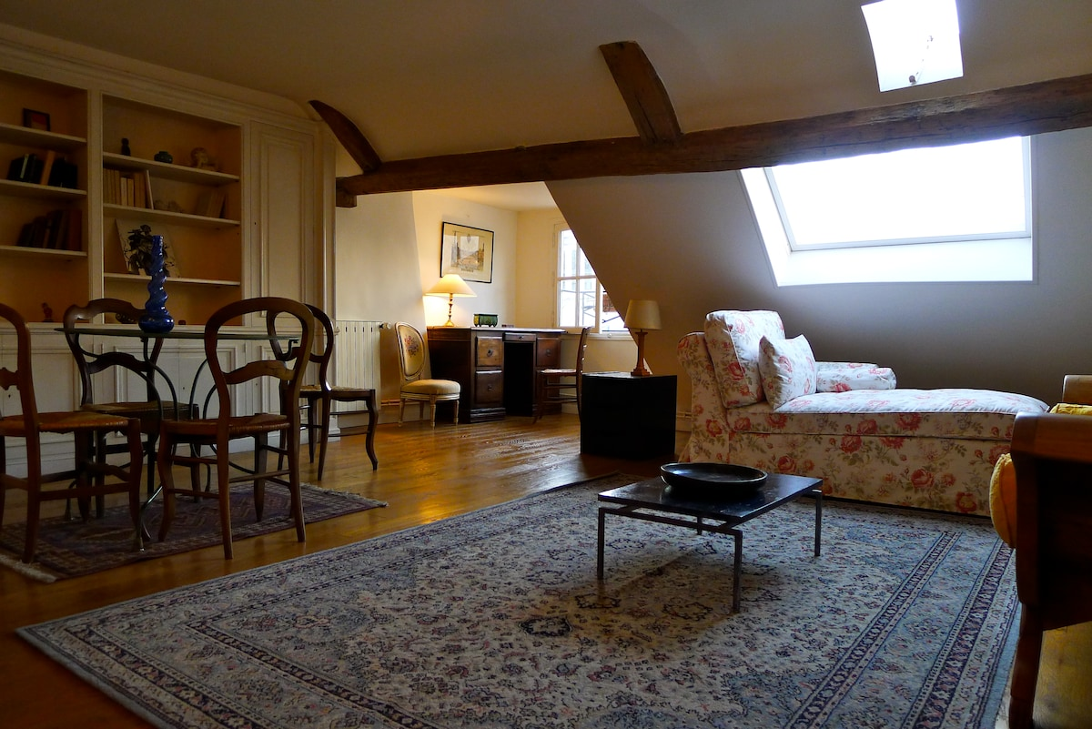Vast living with wooden floor, oriental rugs, library, dining, lounge and desk