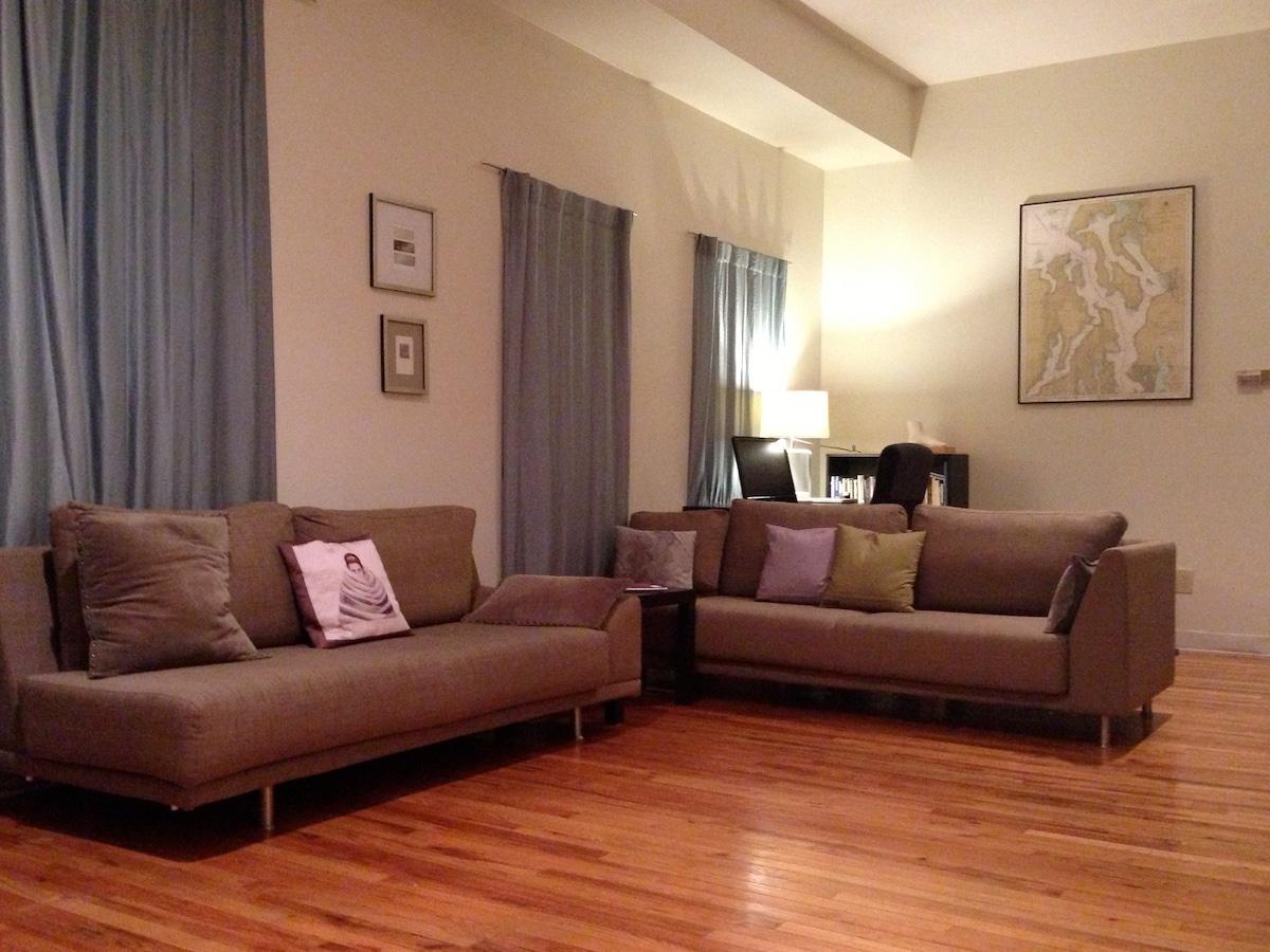Main room seating; in far corner, guest workspace (desk & swivel chair, hi-speed private wi-fi).