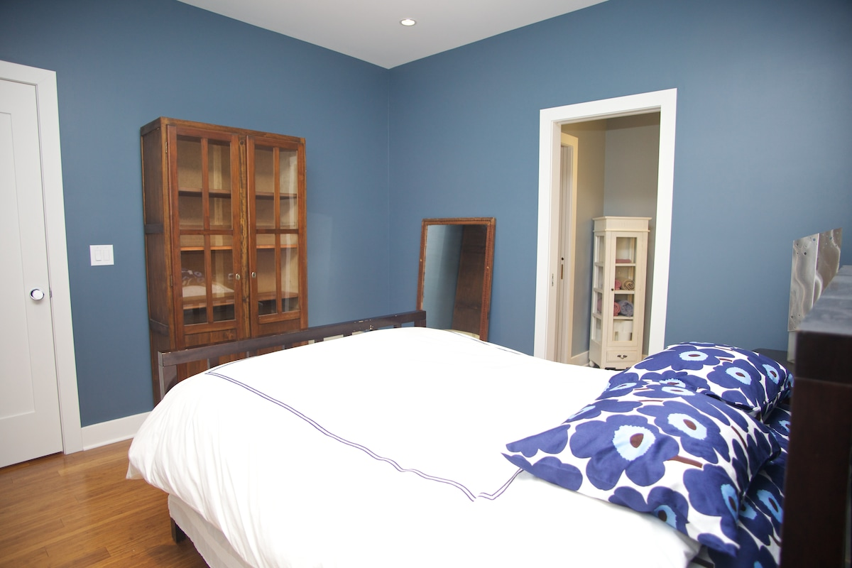 Another view of the bedroom with door on right leading to bathroom.