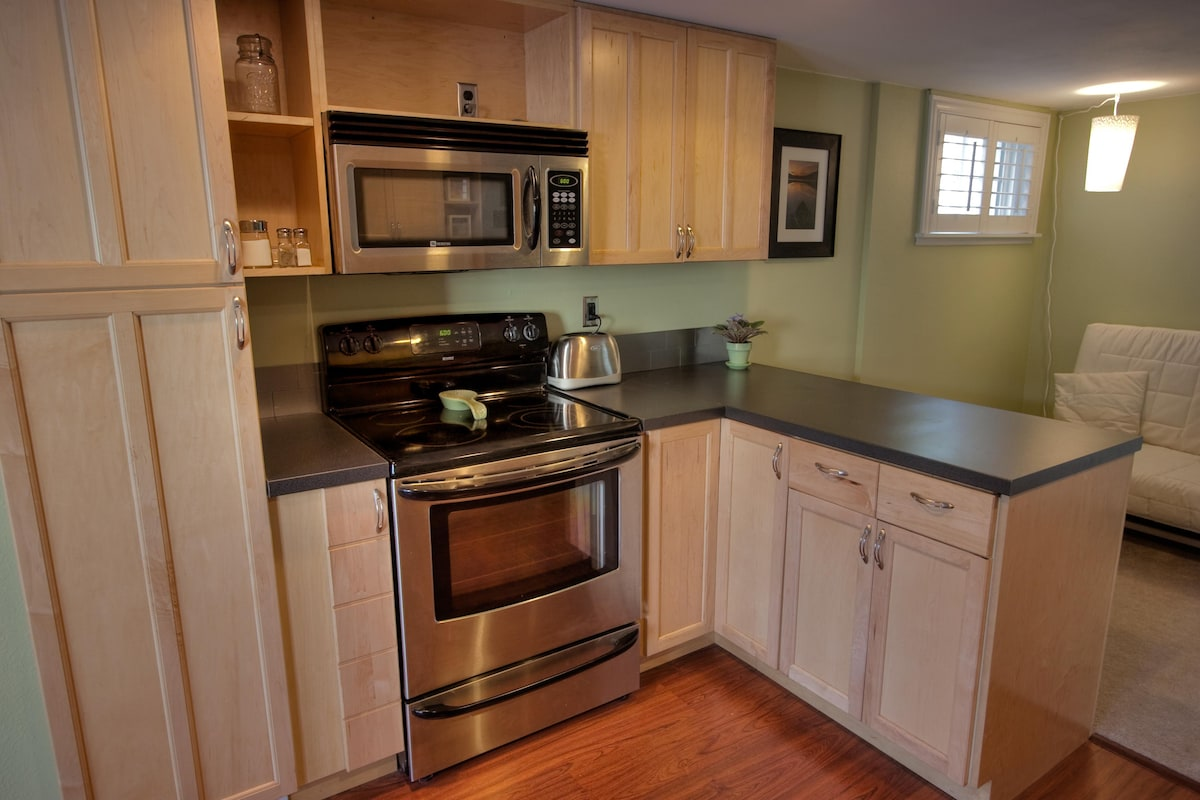 Kitchen stocked with dishes, utensils, cooking needs, coffee maker, coffee and toaster