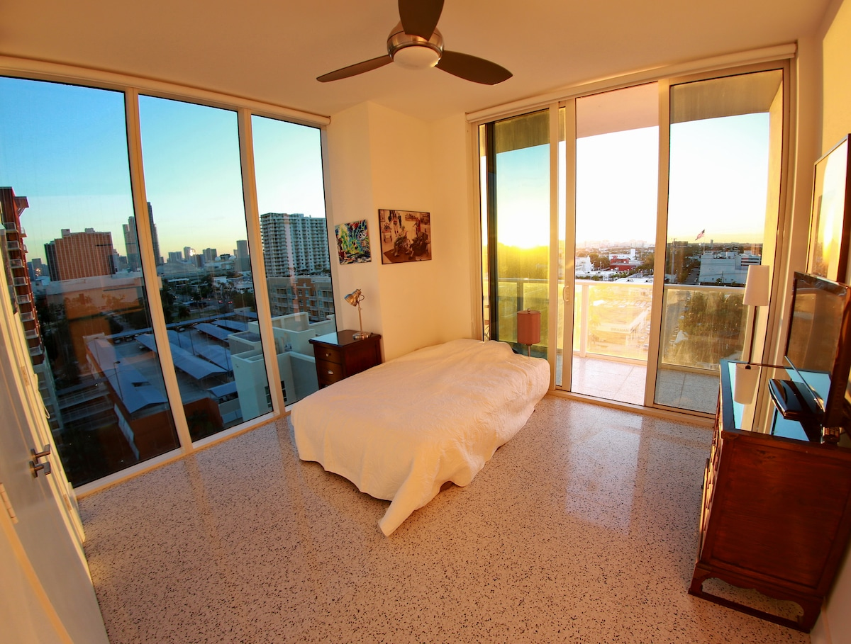 Actual Bedroom offered. 10 foot ceilings/windows to the south and west, Private Balcony. Queen size bed (no headboard to preserve 'airy' feel of room), Nightstand, Desk, TV, Fan, Blackouts on all windows, roomy closet); photo taken just before sunset