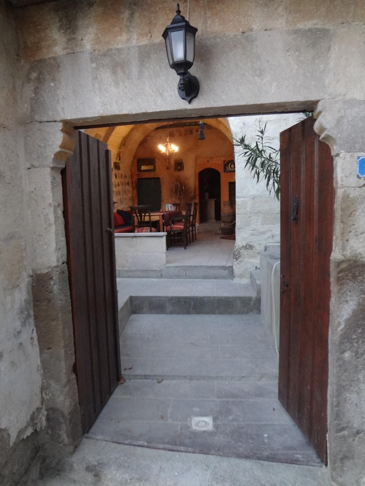 Enter through the porch, over the courtyard and into the house.