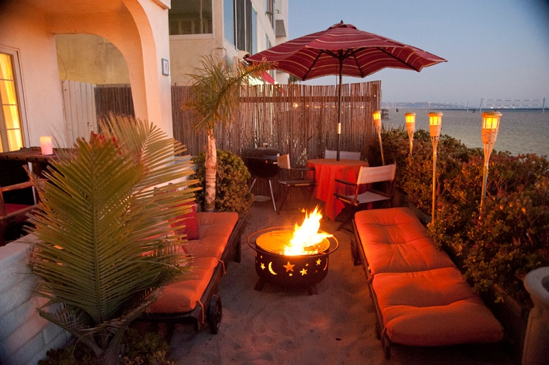 Our magnificent beach front patio at sunset with sun lounge chairs, dining table, tiki torches and fire pit surrounded by palm trees.