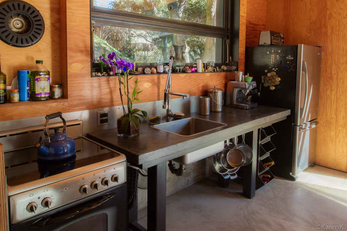 Concrete countertop with restaurant faucet new stainless steel fridge and stove.