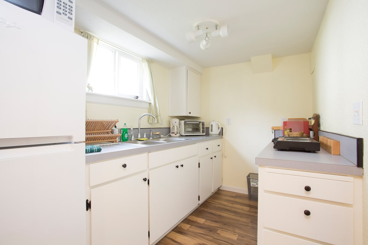 Kitchen with fridge, toaster oven, microwave, electric water kettle and cook top.