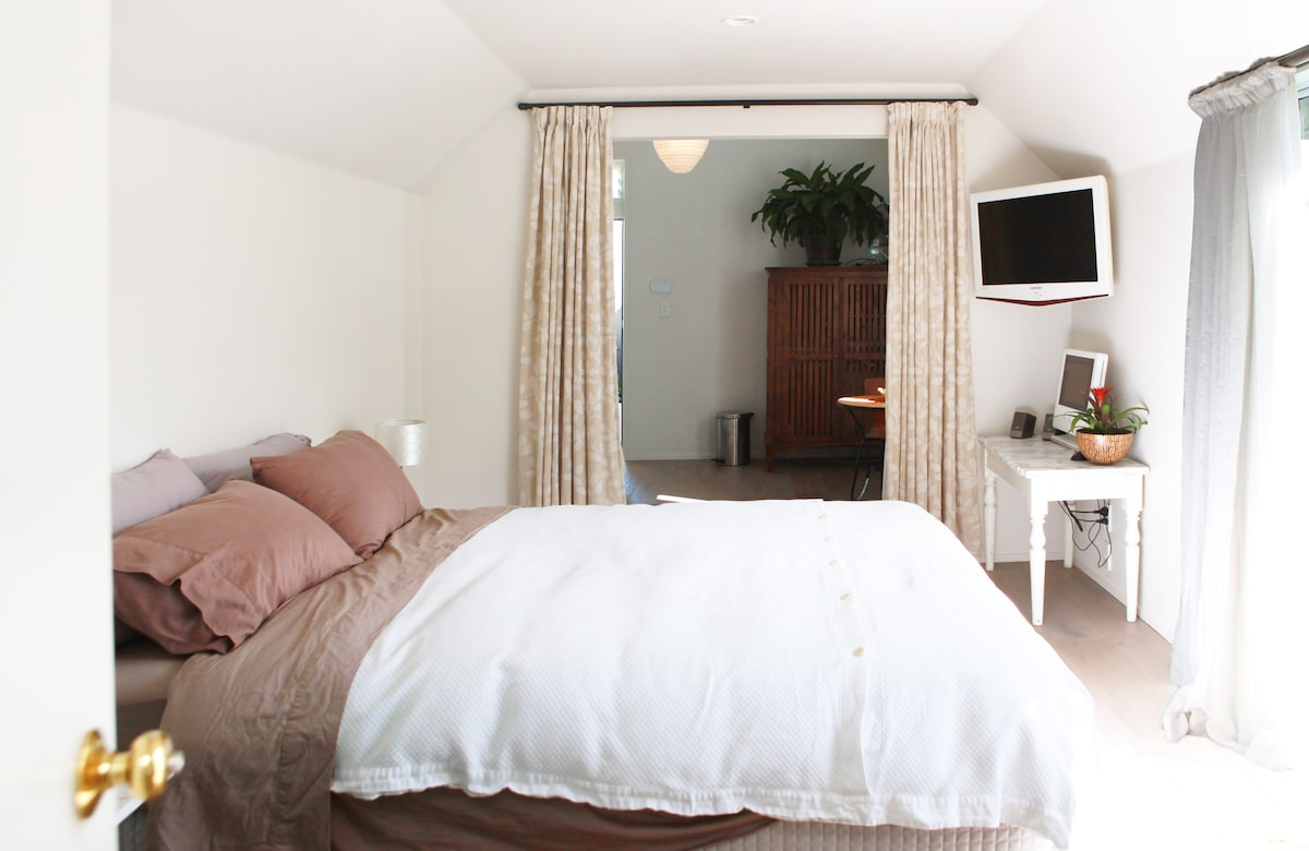 Curtains can be pulled to create separate space between bedroom & living room.