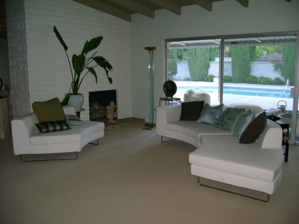 The living room is relaxed with a curving sectional, an understated fireplace and a large volume of natural light.