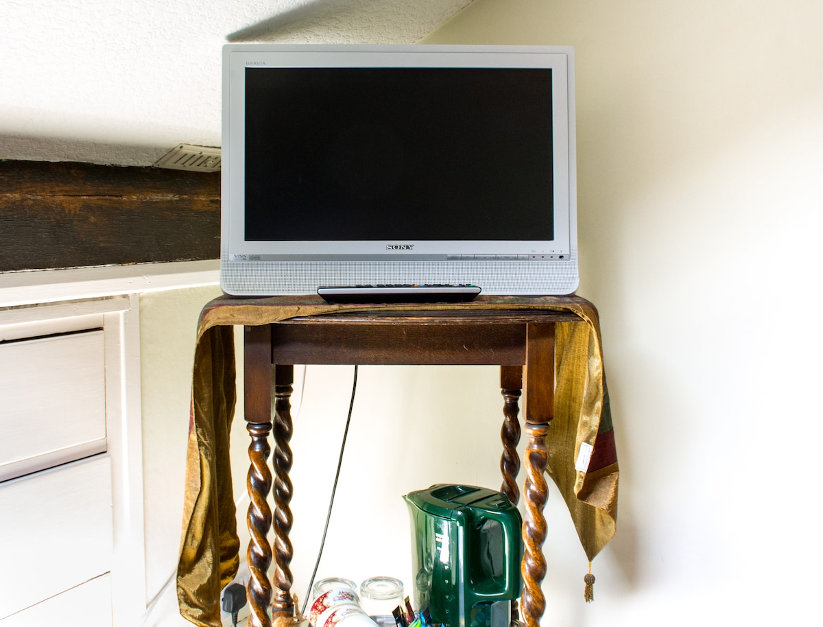 Tucked under the eaves is a set of three drawers. The TV sits on an old occasional table with tea/coffee making facilities on the lower shelf. Guests are able to watch Freeview digital channels and listen to digital radio from the TV.
