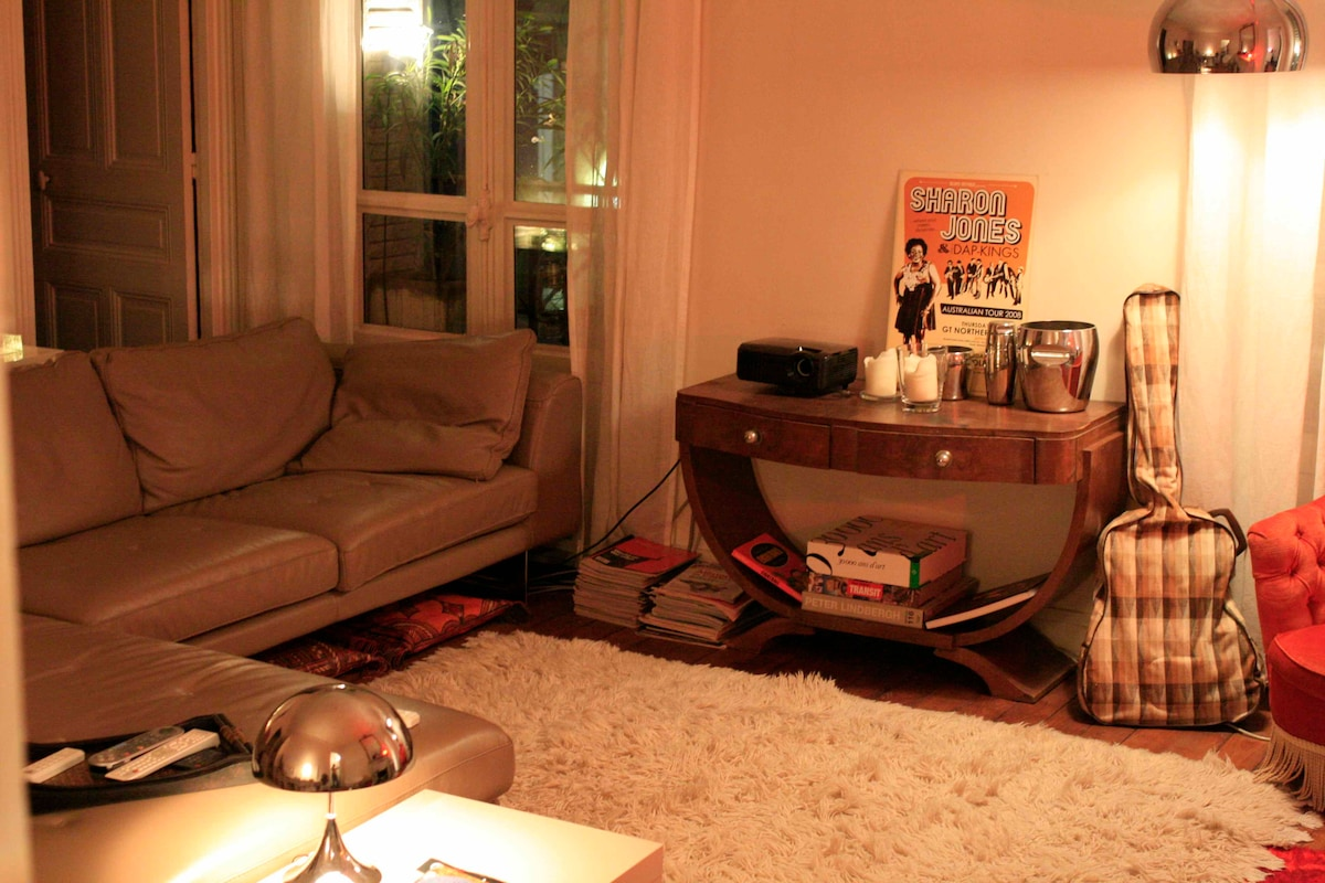 Lounge area with leather sofas, wooden floor and rugs
