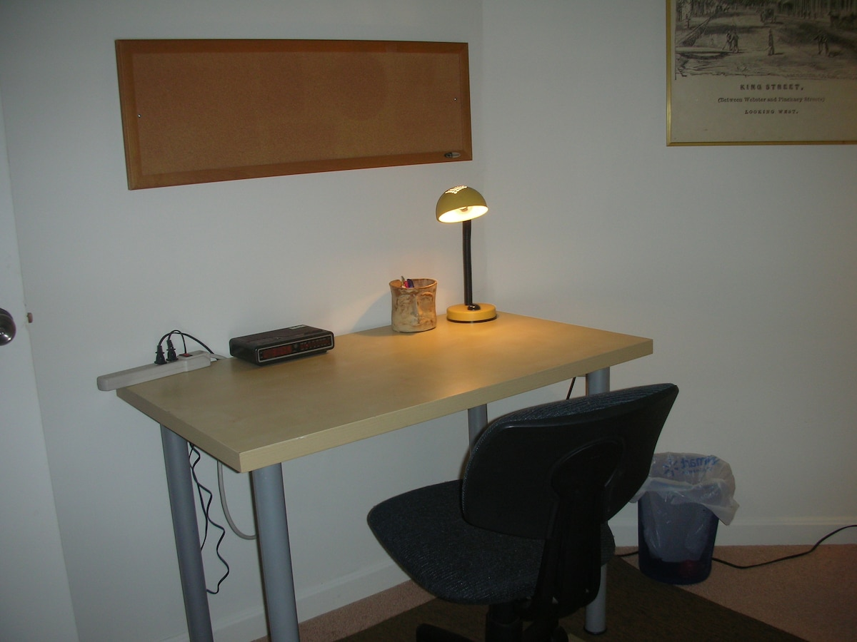Desk with lamp, radio/alarm clock, and a bulletin board.