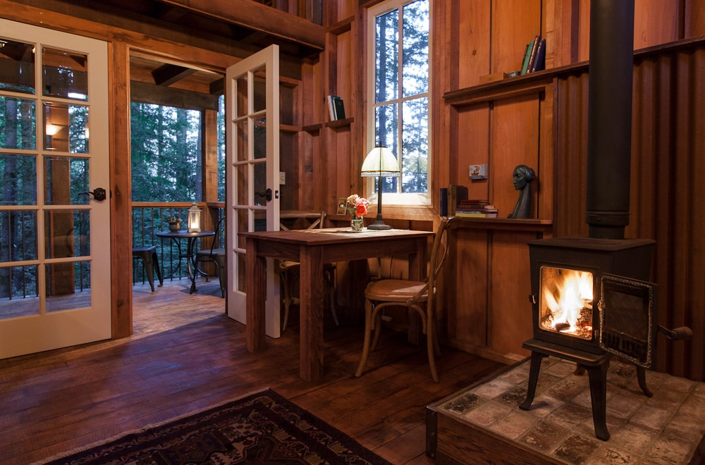 Cabin living area with woodstove, doors to deck, and table ready for your creative projects.