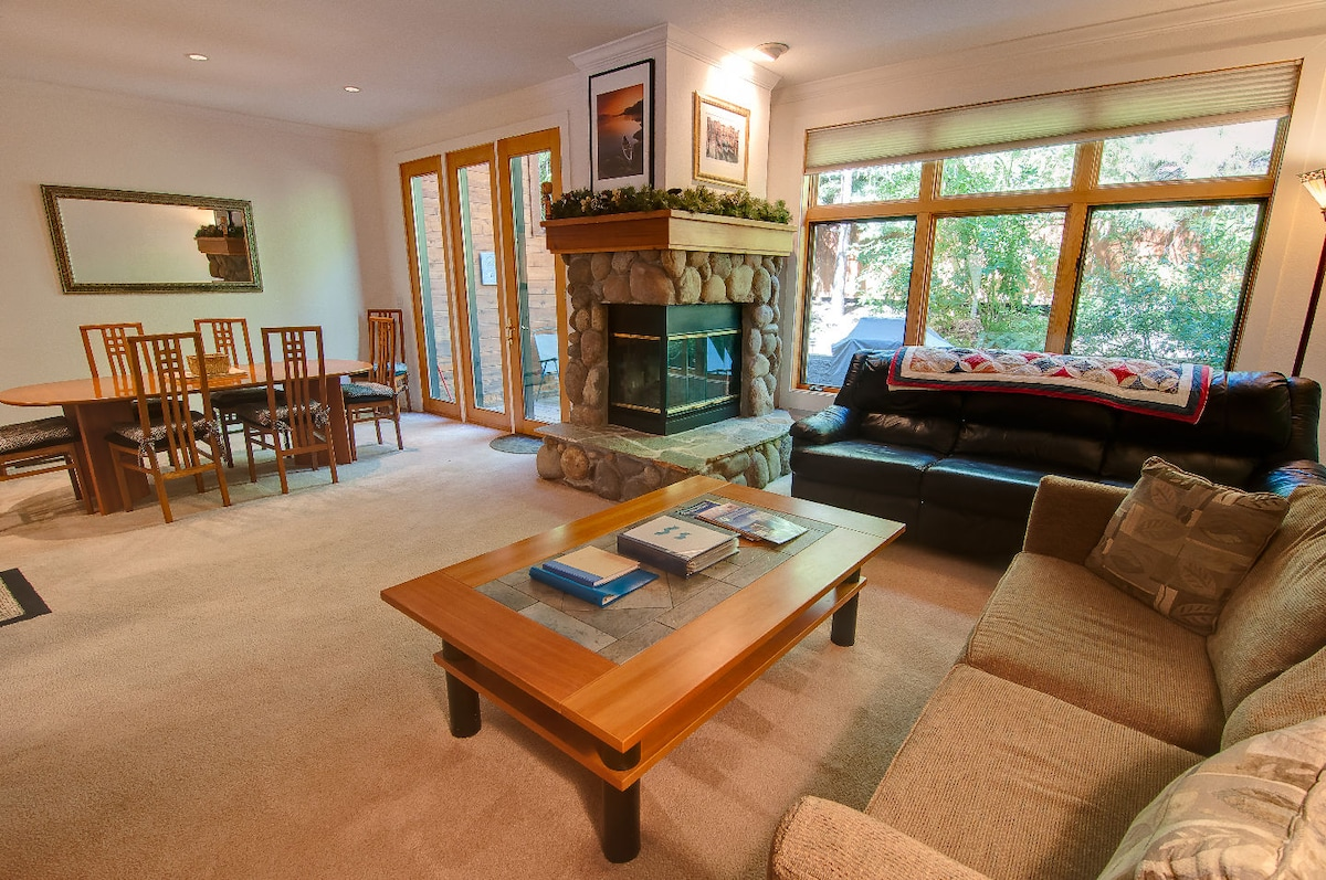 Spacious Family Room with large windows and view of deck and trees.  Gas fireplace.