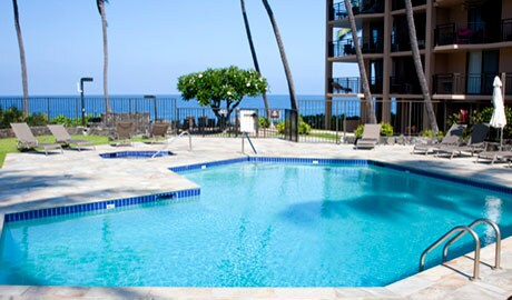 Pool and jacuzzi, chaise lounges and umbrellas are poolside.