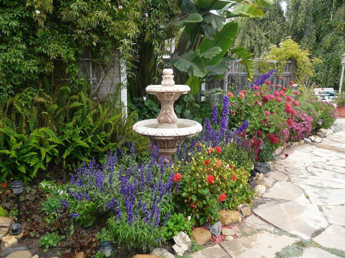 A fountain below the loft lulls the mixed tropical, annual and perennial border garden.