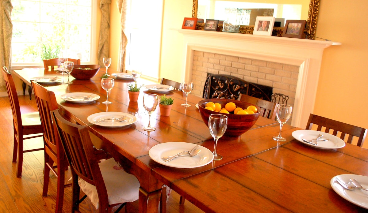 Beautiful Farmhouse dining table set for 10 in front of wood burning fireplace.  House has table settings for 12-14.