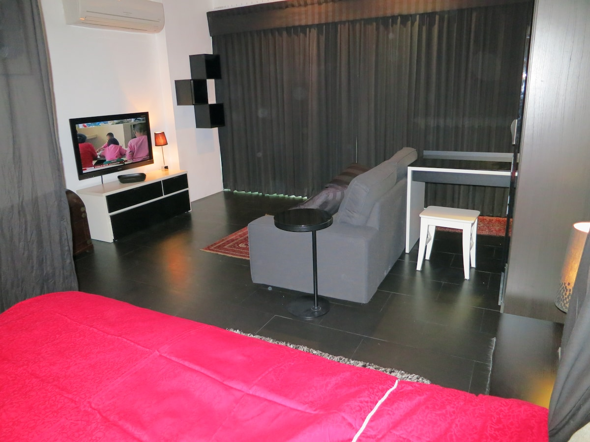 TV-sofa and working desk make the front part of the room. Light proove curtains on the window front change day into night for the resident.