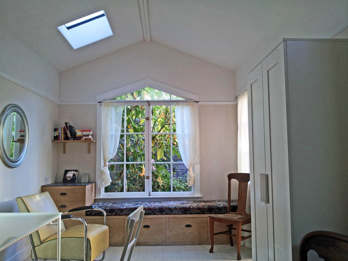 This is the view of the garden from the bed. The glass at the top of the window is hand blown. Light fills the room. The window seat is a comfortable place to stretch out, read, meditate, nap or read.
