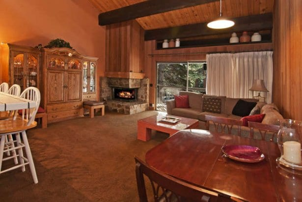 Open concept great room with vaulted beam ceilings and stone fireplace