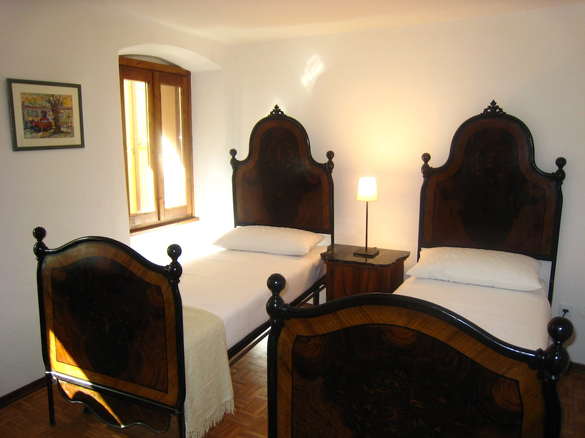 Twin-bedded room features traditionally painted iron 'matrimonial' beds