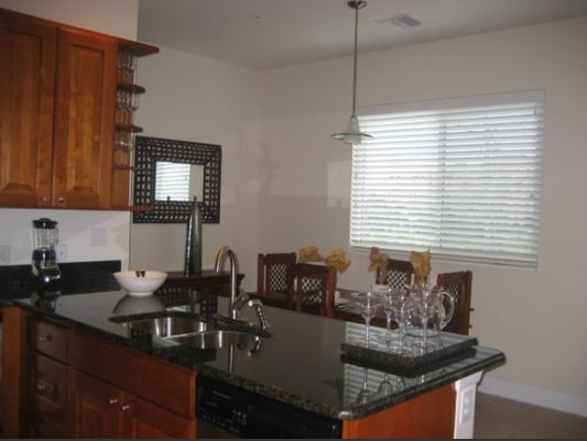 Granite counter tops in the kitchen looking to dining area and window over the marsh between you and the Ritz.