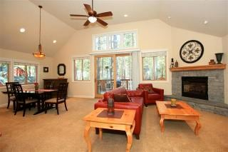 Spacious Great Room that has fire place, access to deck, dining table, and full kitchen.