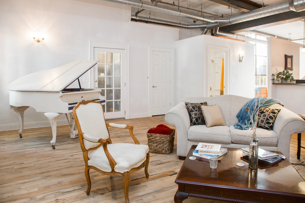 The warehouse suite has a large living space with exposed brick, steel beams, spiral duct, and original wood flooring.
