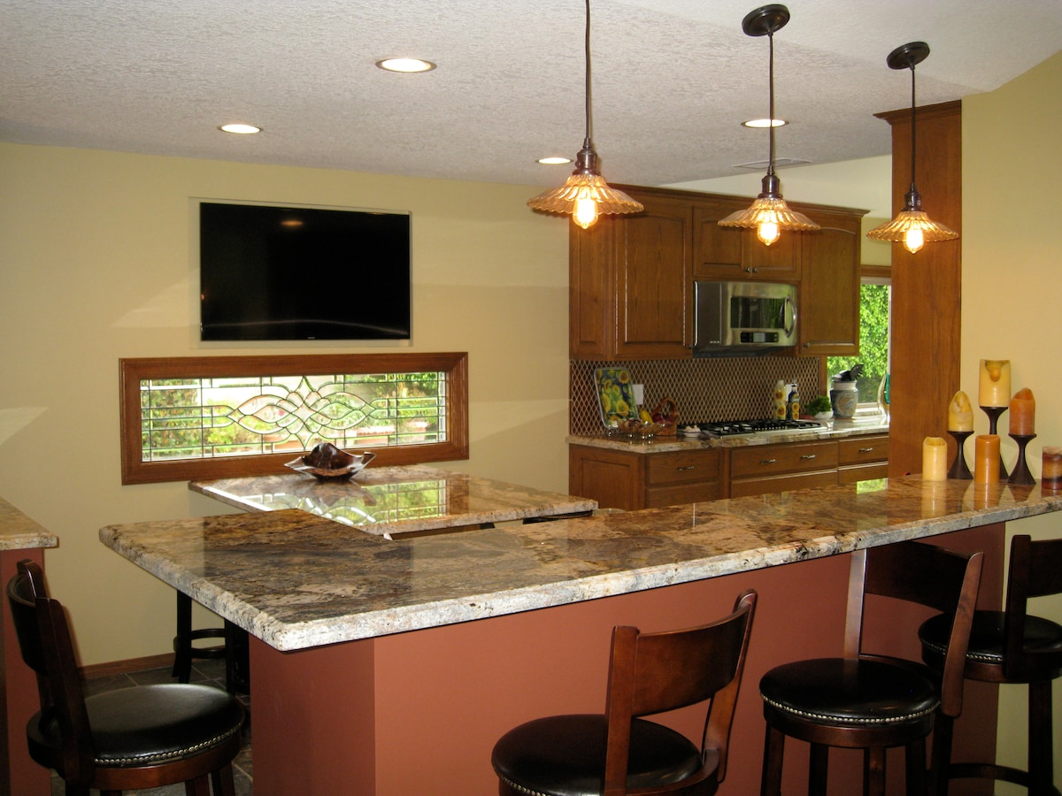 Spacious, upgraded kitchen with gas appliances, double ovens, granite countertops and table, and beautiful, custom windows.