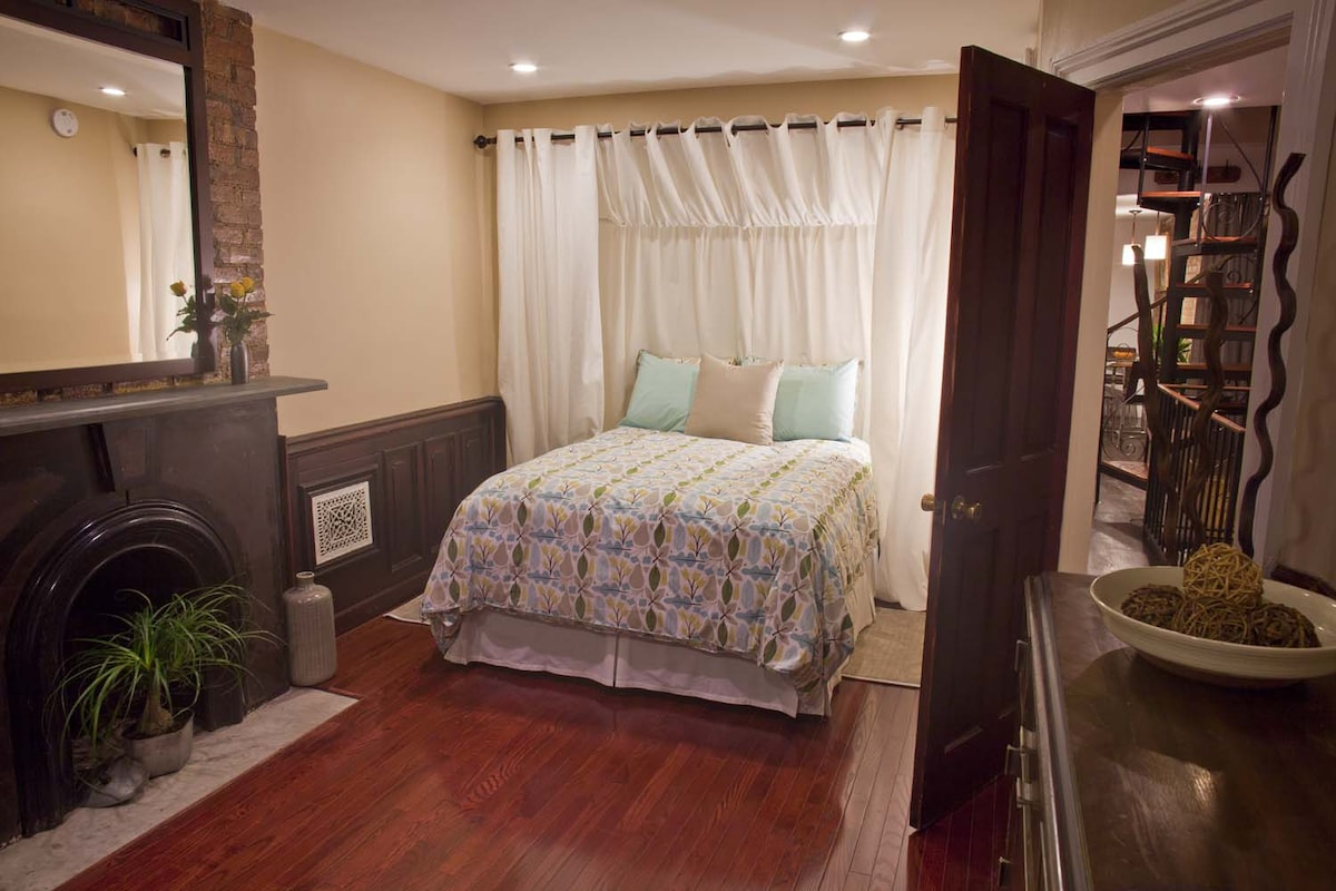 Spacious bedroom with wainscoting, wood flooring and a slate fireplace.