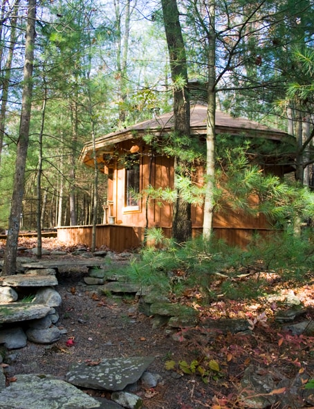 The guest Cabin being offered. View from a joining stone deck. Access is by wooden boardwalks. It has 4 windows and 2 doors, fireplace and queen bed.