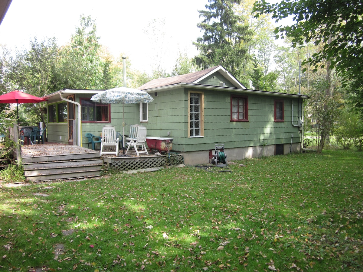 lawned area with a feeling of privacy, large deck and out door tub with hot and cold running water