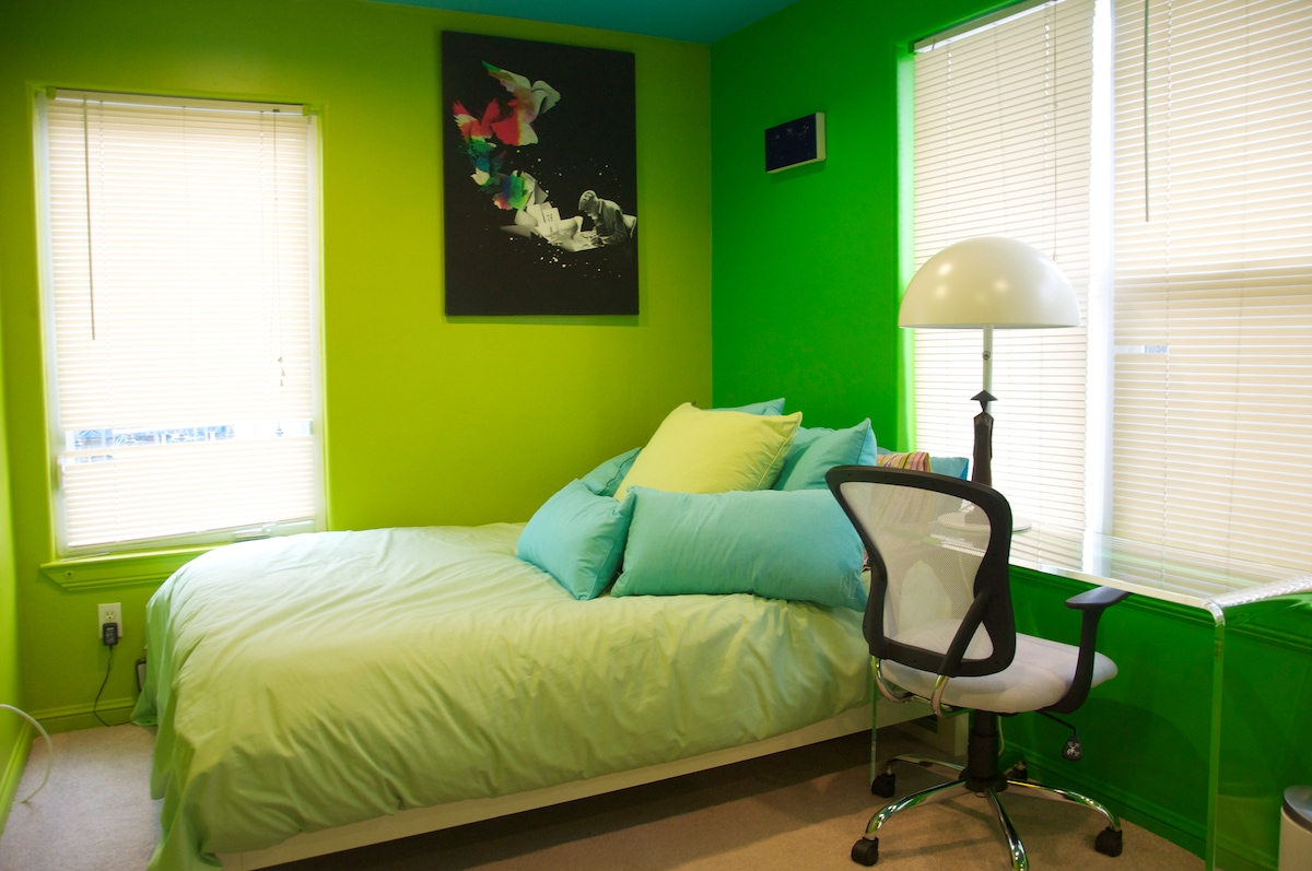 The green room boasts a full-sized bed, an acrylic desk and access to the fire escape.