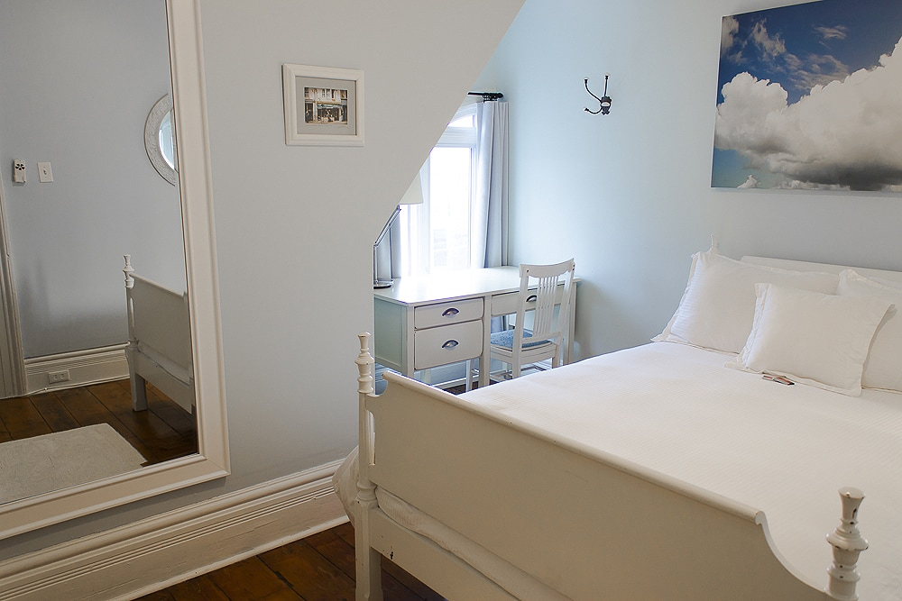 Large wall mirror between the bed and wardrobes.