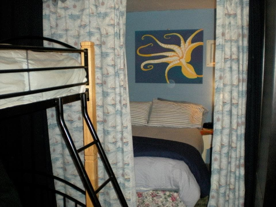 Double bed is tucked in a nook and screened with curtains for privacy.