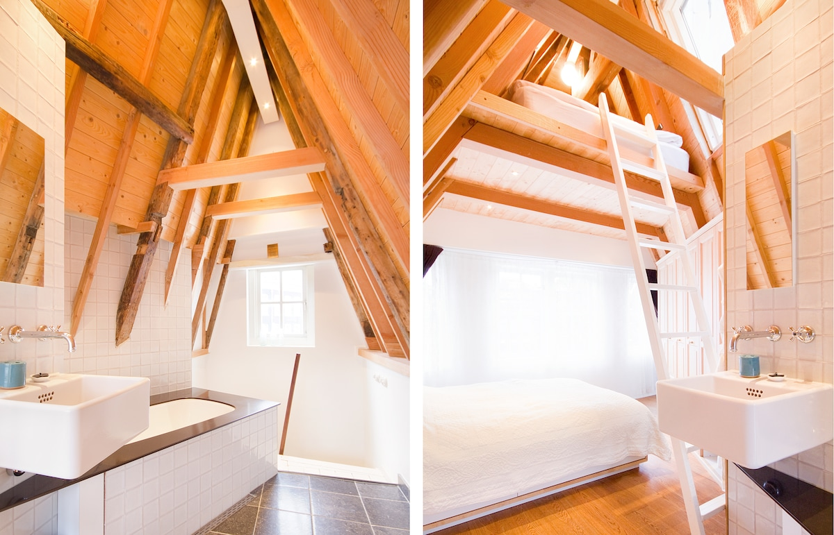 Bathroom with bath and extra double bed under the rafters