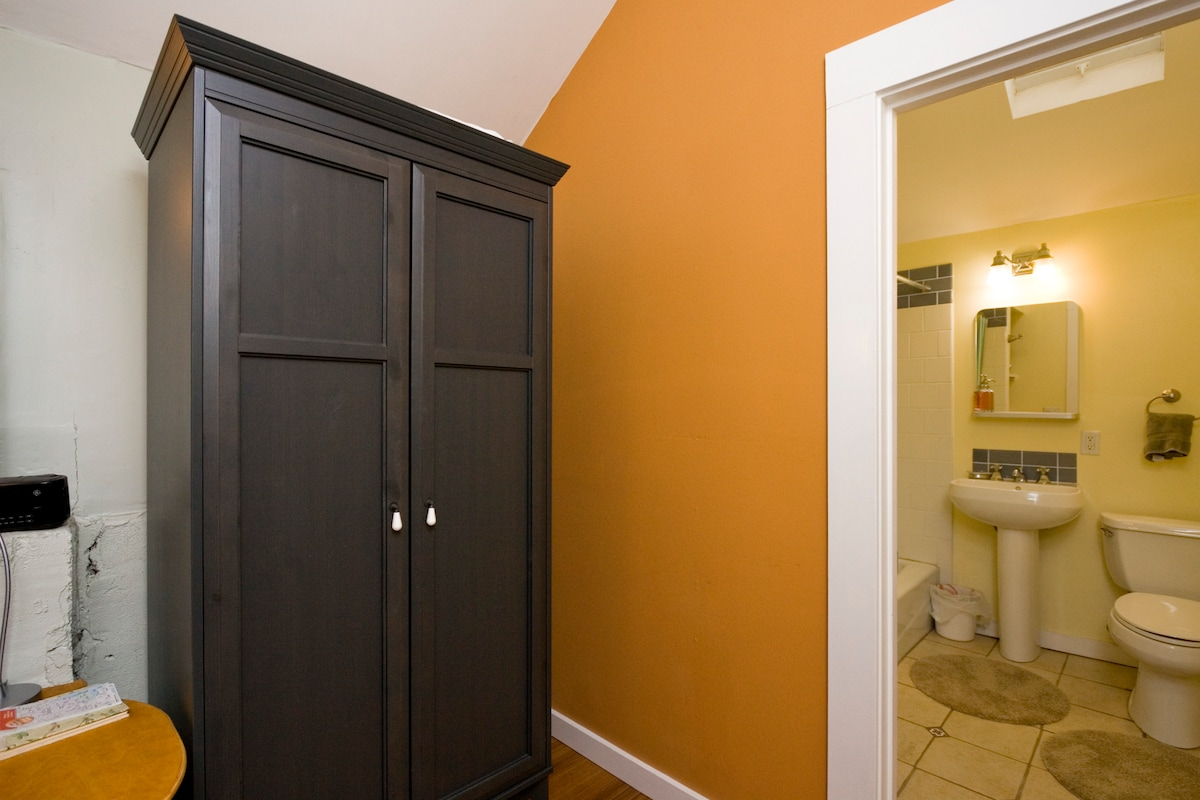 wardrobe behind bed, door to bathroom