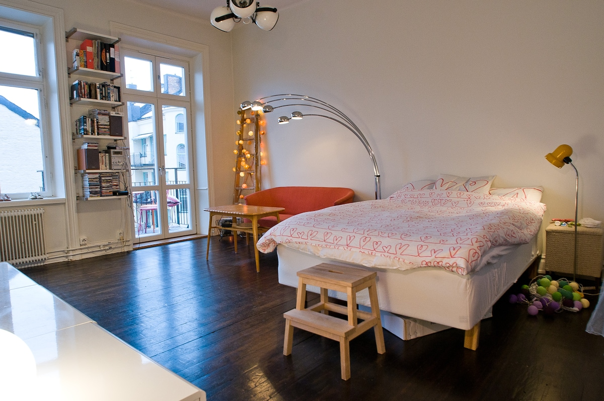 Large, spacious room with a double bed, sofa and sofa table. Doors open out to the balcony.